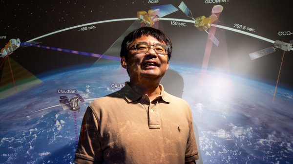 Jun Wang in front of earth with satellites overhead